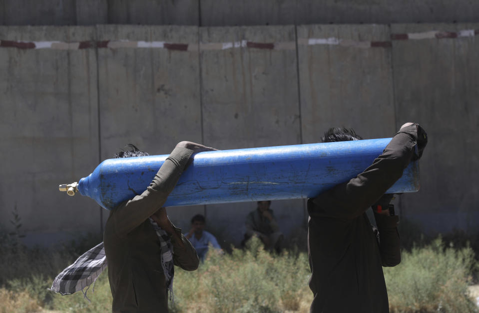 Men carry a cylinder to be refilled from a privately owned oxygen factory, in Kabul, Afghanistan, Saturday, June 19, 2021. Health officials say Afghanistan is fast running out of oxygen as a deadly third surge of COVID worsen. (AP Photo/Rahmat Gul)