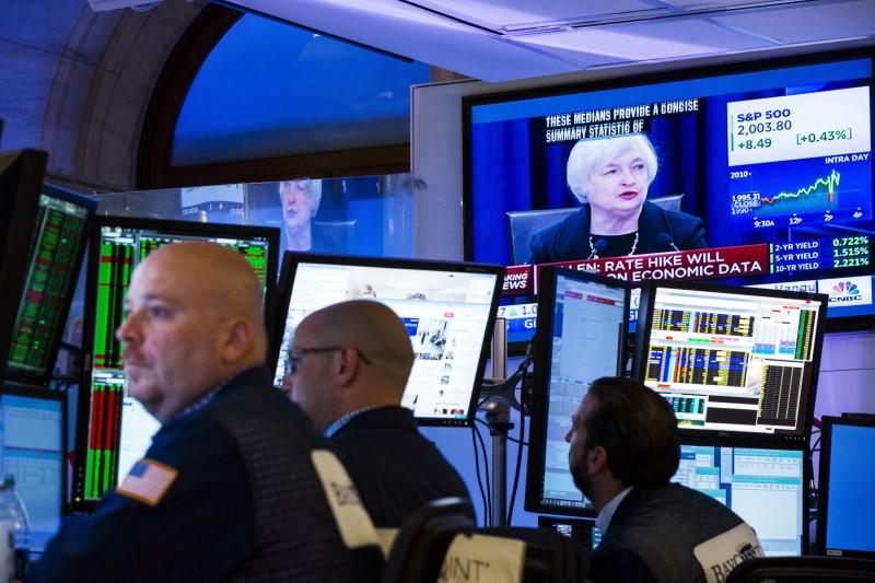Traders work underneath a television screen showing Federal Reserve Chair Janet Yellen announcing that the Federal Reserve will leave interest rates unchanged on the floor of the New York Stock Exchange