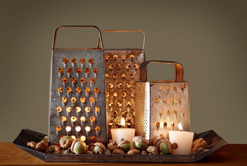<p>Create moody ambience on a sideboard with this flickering display.</p><p><strong>Step 1: </strong>Arrange multiple vintage box graters (we found ours on Etsy) on a tray. Illuminate with flameless flickering LED votives to prevent the metal graters from becoming too hot to handle.</p><p><strong>Step 2: </strong>Fill in gaps on tray with acorns and extra candles. </p>