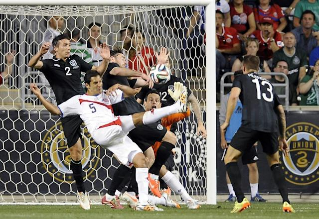 Costa Rica's Celso Borges (5) takes a shot on goal as Ireland's Stephen Kelly (2), Richard Keogh, middle and goal keeper David Forde defend during the first half of an international friendly soccer match on Friday, June 6, 2014, in Chester, Pa. (AP Photo/Michael Perez)