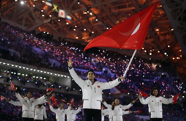 Alper Ucar of Turkey waves the national flag as he leads his team into the stadium during the opening ceremony of the 2014 Winter Olympics in Sochi, Russia, Friday, Feb. 7, 2014. (AP Photo/Matt Dunham)