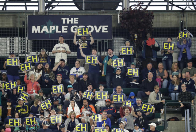 "Fans in the ""Maple Grove,"" the special cheering section for Seattle Mariners starting pitcher James Paxton, who is from Canada, hold up ""EH"" signs during the fourth inning of the team's baseball game against the Detroit Tigers, Saturday, May 19, 2018, in Seattle. (AP Photo/Ted S. Warren)"
