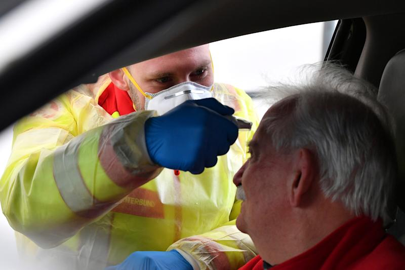 A member of the medical staff measures the temperature of a traveller at a autobahn park place near Gries am Brenner, Austrian province of Tyrol, at border crossing with Italy on Tuesday, March 10, 2020. Austria authorities started on random checks of arriving vehicles at the border crossings with Italy in reaction to the outbreak of the new coronavirus in Europe, particularly in Italy. As part of the move, officials measure the temperatures of some passengers in cars, trucks and buses. For most people, the new coronavirus causes only mild or moderate symptoms, such as fever and cough. For some, especially older adults and people with existing health problems, it can cause more severe illness, including pneumonia. (AP Photo/Kerstin Joensson )