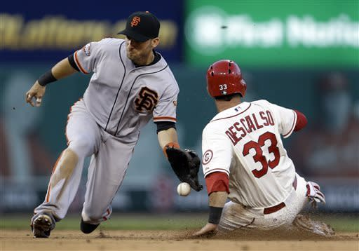 St. Louis Cardinals' Daniel Descalso, right, is safe at second for a stolen base as San Francisco Giants second baseman Marco Scutaro misses the throw during the sixth inning of the second game of a baseball doubleheader on Saturday, June 1, 2013, in St. Louis. (AP Photo/Jeff Roberson)