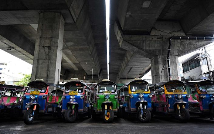"""This photo taken on July 20, 2021 shows rows of """"tuk-tuks"""" in a parking lot, as drivers remain out of work due to the economic hardship of Covid-19 and more than a year of no incoming foreign tourism, in Bangkok. - Tuk-tuks sitting idle, taxis crammed into empty lots -- just some of the vehicles taken off Bangkok's normally riotous roads and stashed in storage as a Covid surge decimates tourism and travel, leaving drivers out of pocket. - AFP"""