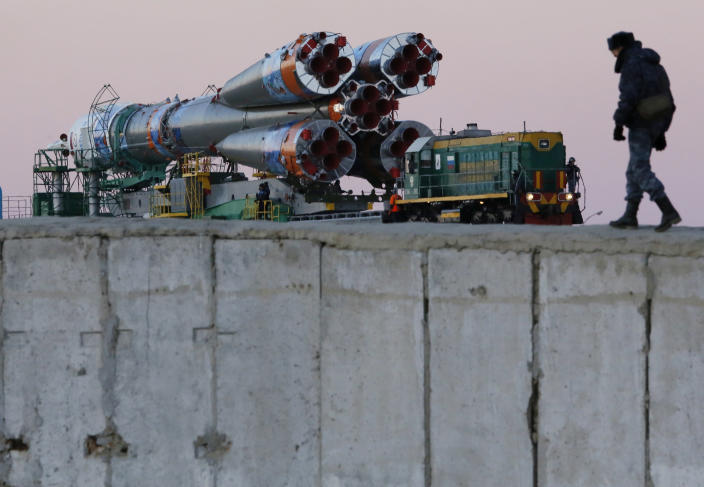 A Russian policemen guard Russia's Soyuz-FG booster rocket with the space capsule Soyuz TMA-11M that will carry a new crew to the International Space Station (ISS), as the rocket is transported from hangar to the launch pad at the Russian leased Baikonur cosmodrome, Kazakhstan, Tuesday, Nov. 5, 2013. The rocket is emblazoned with the emblem of the Winter Olympics in Sochi. For the first time, it will also carry an Olympic torch to space as part of the ongoing Olympic torch relay. The torch will be brought back along with the station's current crew. The rocket is scheduled to blast off on Thursday, Nov.7. (AP Photo/Dmitry Lovetsky)