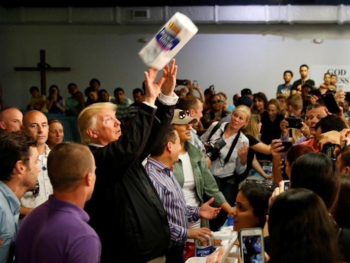 US President Donald Trump tosses rolls of paper towels to people at a hurricane relief distribution centre at Calvary Chapel in San Juan: Jonathan Ernst/Reuters