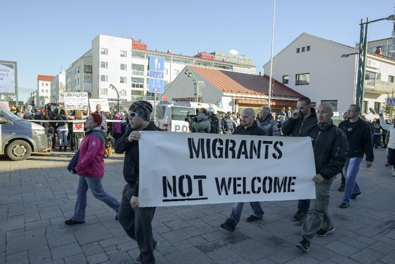 A protester holds a banner reading 'Migrants not welcome' during an anti-migrant rally in Tornio, Finland on October 3, 2015 (AFP Photo/Panu Pohjola)
