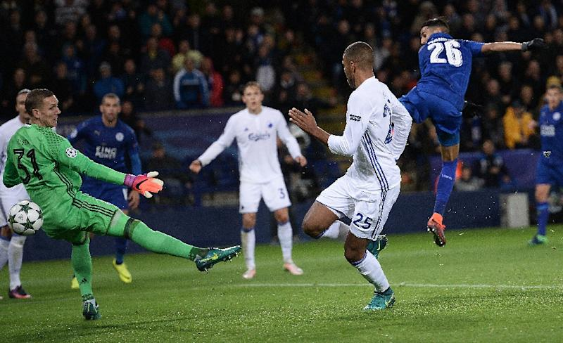 Leicester City's Riyad Mahrez (R) shoots past FC Copenhagen's  goalkeeper Robin Olsen (L) to scores his team's first goal during at the King Power Stadium in Leicester, central England on October 18, 2016