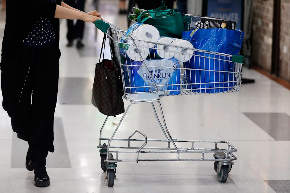 A customer pushes a shopping cart containing toilet paper at a supermarket in Sydney.