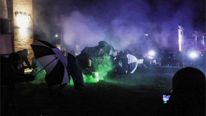 Protesters shelter from tear gas in Brooklyn Center, Minnesota, April 13, 2021