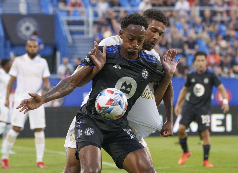 Atlanta United defender George Bello, rear, hangs on to CF Montreal forward Mason Toye during the first half of an MLS soccer match Wednesday, Aug. 4, 2021, in Montreal. (Paul Chiasson/The Canadian Press via AP)
