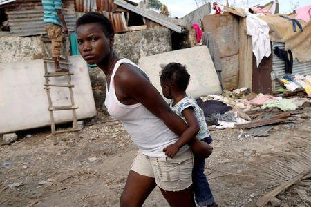 A woman carries a child as they walk in front of destroyed houses after Hurricane Matthew passes Jeremie, Haiti, October 7, 2016. REUTERS/Carlos Garcia Rawlins