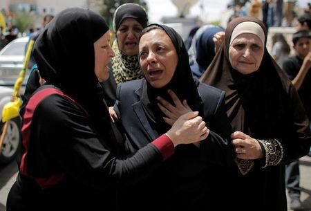 FILE PHOTO: The mother (C) of 17-year-old Palestinina Nadim Nuwara mourns during his funeral in the occupied West Bank in Ramallah May 16, 2014. REUTERS/Ammar Awad/File Photo