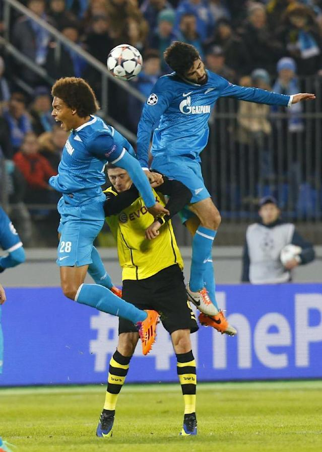 Zenit's Axel Witsel, left, and Luis Neto, right, go for a header over Borussia's Robert Lewandowski during the Champions League soccer match between Zenit St.Petersburg and Borussia Dortmund at Petrovsky stadium in St.Petersburg, Russia, on Tuesday, Feb. 25, 2014. (AP Photo/Dmitry Lovetsky)