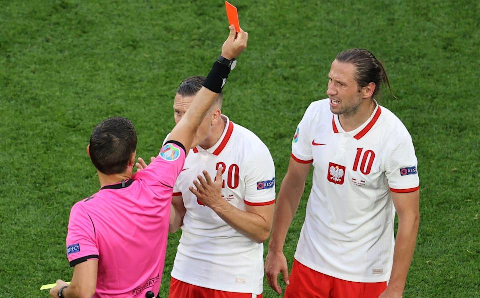 A referee Ovidiu Hategan gives a red card to Poland's Grzegorz Krychowiak, right, during the Euro 2020 soccer championship group E match between Poland and Slovakia at Gazprom arena stadium in St. Petersburg, Russia, Monday, June 14, 2021 - Anton Vaganov/Pool via AP