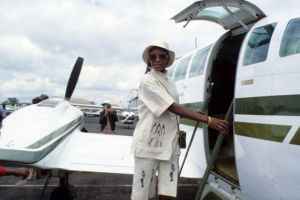 <p>British model Maizie Williams boards a small plane in Nairobi, Kenya in 1978 in a chic linen suit and matching hat. </p>