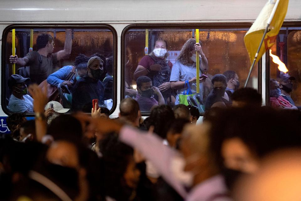 Passengers on a bus look to people protesting against a police operation to combat alleged drug traffickers Thursday in which 25 people were killed, at the Jacarezinho favela in Rio de Janeiro, Brazil, on May 7, 2021. - 25 people including a police officer were killed yesterday during a police operation against drug traffickers in the Jacarezinho favela. The incident began with an exchange of fire at a metro station in the area which is in the North Zone of Rio de Janeiro. (Photo by MAURO PIMENTEL / AFP) (Photo by MAURO PIMENTEL/AFP via Getty Images)