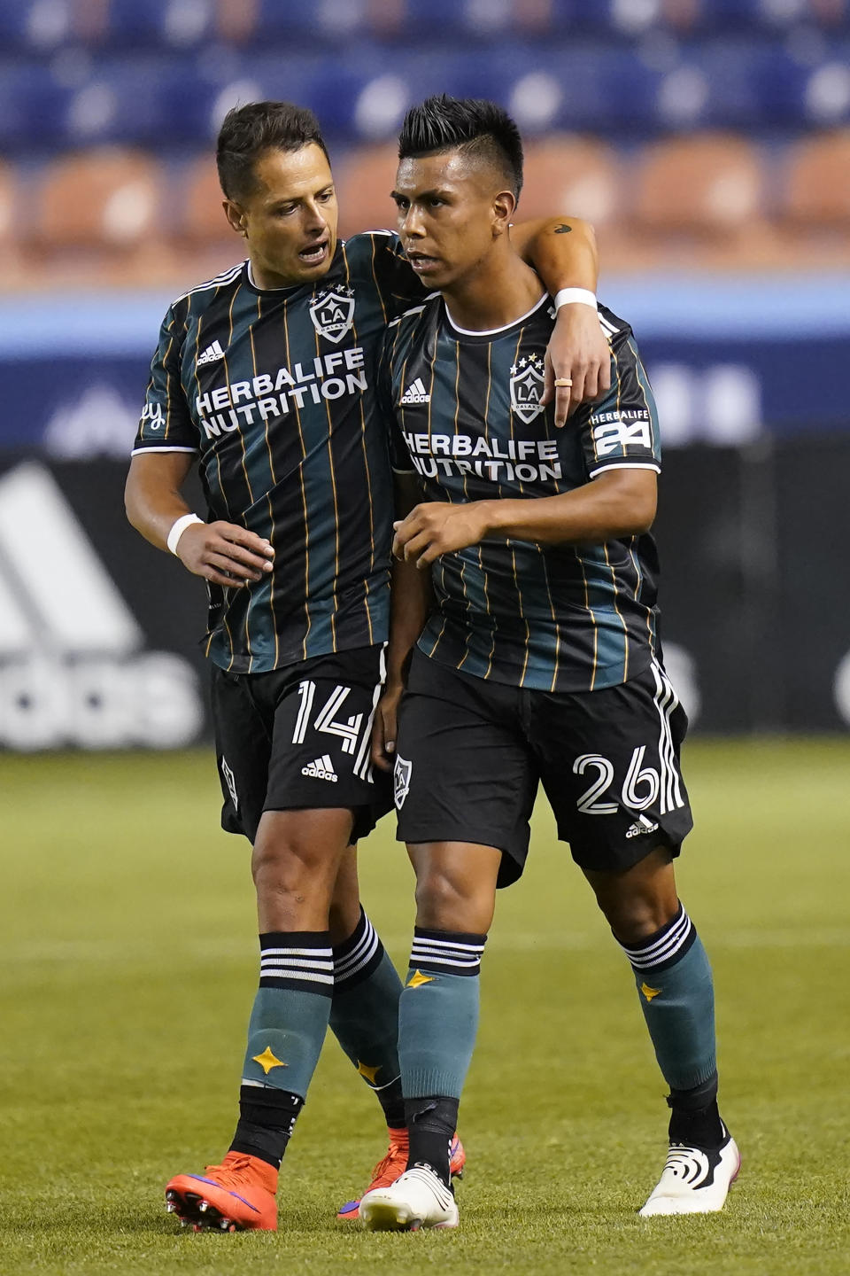 Los Angeles Galaxy's Efrain Alvarez (26) celebrates with Chichartio (14) after scoring against the Vancouver Whitecaps in the second half during an MLS soccer match Wednesday, June 23, 2021, in Sandy, Utah. (AP Photo/Rick Bowmer)