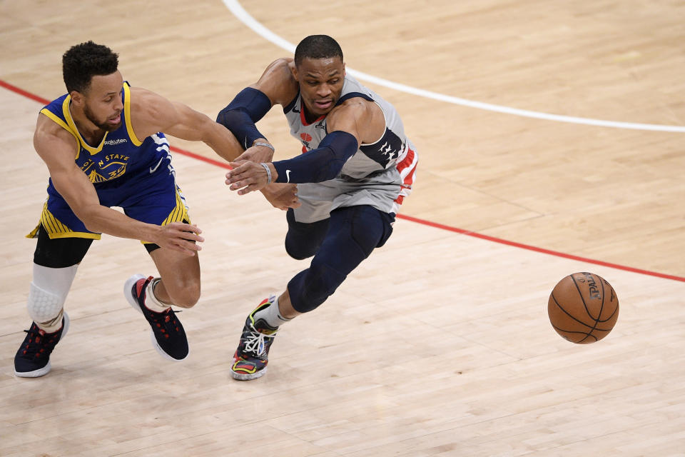 Golden State Warriors guard Stephen Curry (30) and Washington Wizards guard Russell Westbrook, right, chase a loose during the first half of an NBA basketball game, Wednesday, April 21, 2021, in Washington. (AP Photo/Nick Wass)