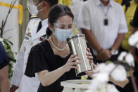 Ballsy Aquino-Cruz holds the urn of her brother former Philippine President Benigno Aquino III before he is placed on the tomb on Saturday, June 26, 2021 at a memorial park in suburban Paranaque city, Philippines. Aquino was buried in austere state rites during the pandemic Saturday with many remembering him for standing up to China over territorial disputes, striking a peace deal with Muslim guerrillas and defending democracy in a Southeast Asian nation where his parents helped topple a dictator. He was 61. (AP Photo/Aaron Favila)