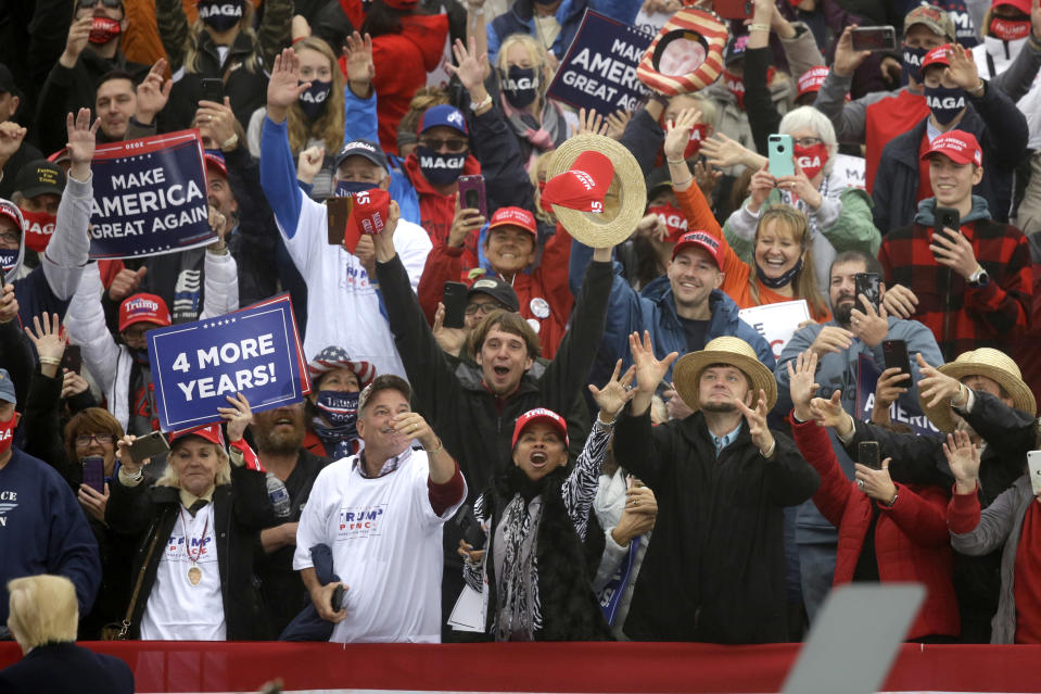 Supporters reach for a hat thrown by President Donald Trump at the conclusion of a rally at Lancaster Airport, Monday, Oct. 26, 2020 in Lititz, Pa. (AP Photo/Jacqueline Larma)