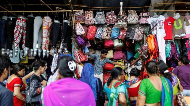 People shop for bags and clothes at roadside shops in a market in Mumbai