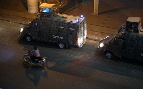 Police vehicles are seen in central Cairo as protesters gather shouting anti-government slogans in Cairo - Credit: Reuters