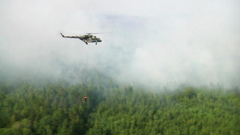 A still image, taken from a video footage shows a helicopter dropping water over a burning forest in Krasnoyarsk region, Russia August 4, 2019. Video footage taken August 4, 2019. REUTERS via Reuters TV