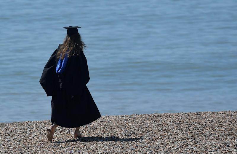 A woman wearing a 'mortar board' hat walks on the beach, following a graduation ceremony for students at University of Brighton, in Brighton, southern Britain, August 3, 2018. (Photo: REUTERS/Toby Melville)