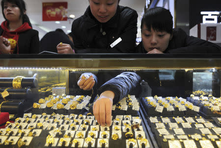 Sales assistants reach for gold rings in a glass case to show to customers at a jewellery store in Hefei, Anhui province February 23, 2011. REUTERS/Stringer/File Photo