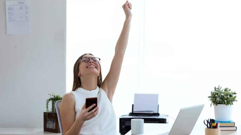 young woman celebrating a victory while working with mobile phone in the office