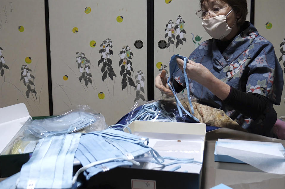 In this image from video, Yoshiko Ogura, 73, sorts out indigo dyed silk masks she produces at her house in Minamisoma, Fukushima Prefecture, northeastern Japan, on Feb. 20, 2021. After the Fukushima nuclear plant disaster a decade ago, nearby farmers weren't allowed to grow crops for two years because of radiation. After the restriction was lifted, two farmers in the town of Minamisoma found an unusual way to rebuild their lives and help their destroyed community. Kiyoko Mori and Ogura planted indigo and soon began dying fabric with dye produced from the plants. (AP Photo/Chisato Tanaka)