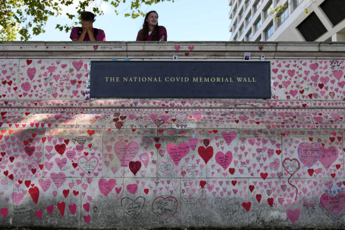 FILE - In this XXX, file photo, nurses from the nearby hospital rest atop the National Covid Memory Wall in London. Britain's Conservative government is hoping a combination of relatively high vaccination rates and common-sense behavior will keep a lid on coronavirus infections this fall and winter and avoid the need for restrictive measures. That plan employs a lighter touch than most nations. (AP Photo/Frank Augstein, File)