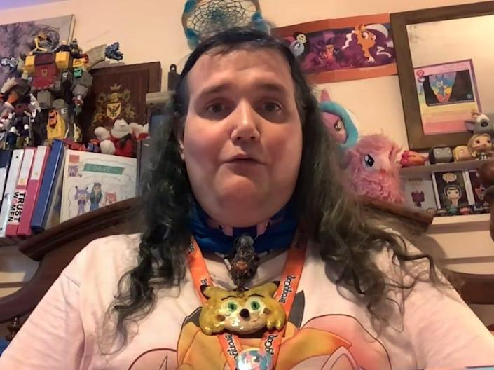 christine chandler, chris chan, looking at the camera with a wall of memerobilia behind her