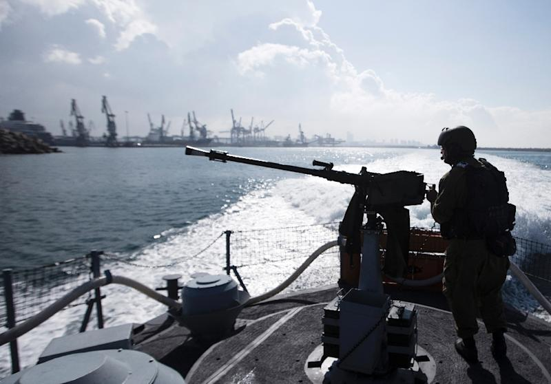 A sailor with the Israeli navy takes a position on vessel as it leaves the port in Ashdod on November 17, 2014