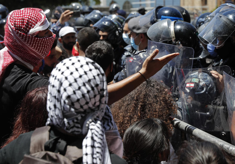 An anti-government protester argues with riot police during a protest against a general amnesty law being proposed in parliament, in Beirut, Lebanon, Thursday, May 28, 2020. (AP Photo/Hussein Malla)