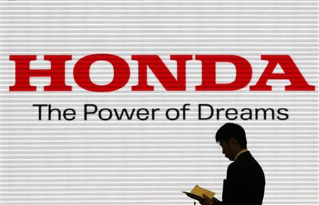 File photo of a man being silhouetted against a logo of Honda Motor at the company showroom in Tokyo