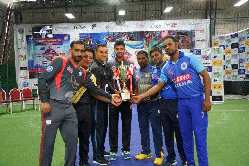 The Captains of Singapore, Singapore A, New Zealand, India, Sri Lanka, UAE and Malaysia pose with the NZ-Asia Cup Trophy (Image Courtesy: Singapore Cricket Association)