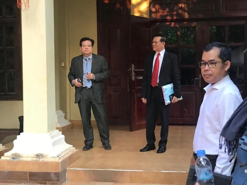Cambodian opposition leader Kem Sokha, center, waits before he heads to the court in his home, in Phnom Penh, Cambodia, Wednesday, Jan. 15, 2020. The trial of the top opposition leader charged with treason began Wednesday, more than two years after he was arrested in what is widely seen as a politically motivated prosecution. (AP Photo/Cheang Sopheng)