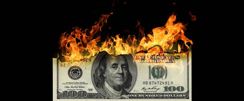 $100 American bill set on fire and burning