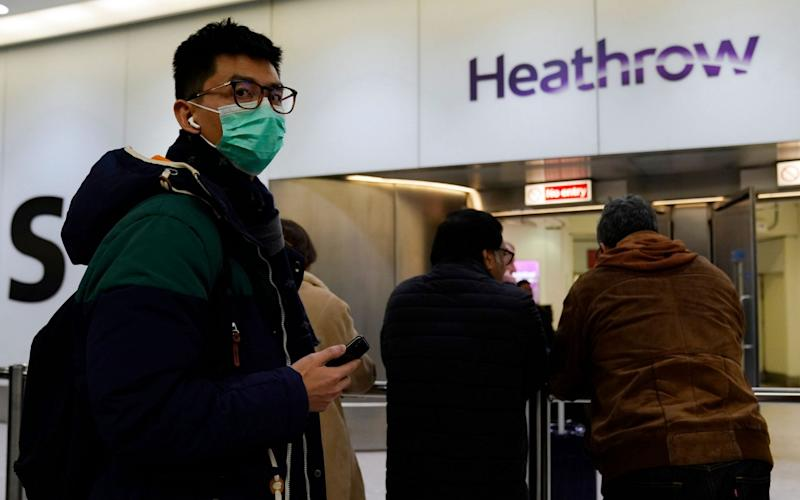 A passenger arrives wearing a mask at Terminal 4, Heathrow Airport - REX