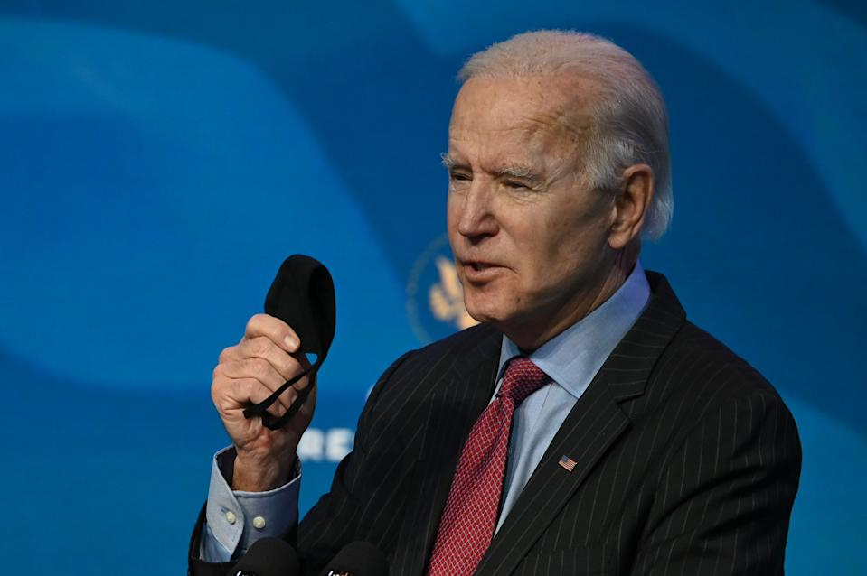 US President-elect Joe Biden holds his facemask as he answers questions from the media about the Covid-19 pandemic at The Queen theater in Wilmington, Delaware on January 8, 2021. - Biden and Harris announced on January 8, 2021 the following nominees for their economic and jobs team: for Secretary of Commerce, Rhode Island Governor Gina Raimondo; for Secretary of Labor, Boston Mayor Marty Walsh; for Small Business Administrator, California official Isabel Guzman; and for Deputy Secretary of Commerce, Biden's former counselor Don Graves. (Photo by JIM WATSON / AFP) (Photo by JIM WATSON/AFP via Getty Images)