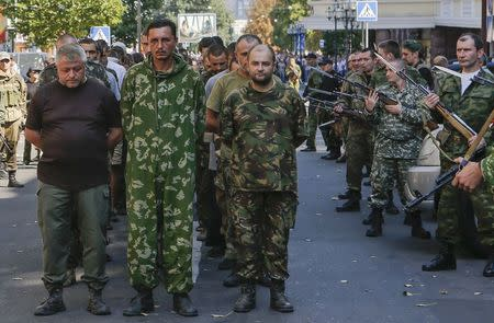 Armed pro-Russian separatists (R) escort a column of Ukrainian prisoners of war as they walk across central Donetsk August 24, 2014. REUTERS/Maxim Shemetov