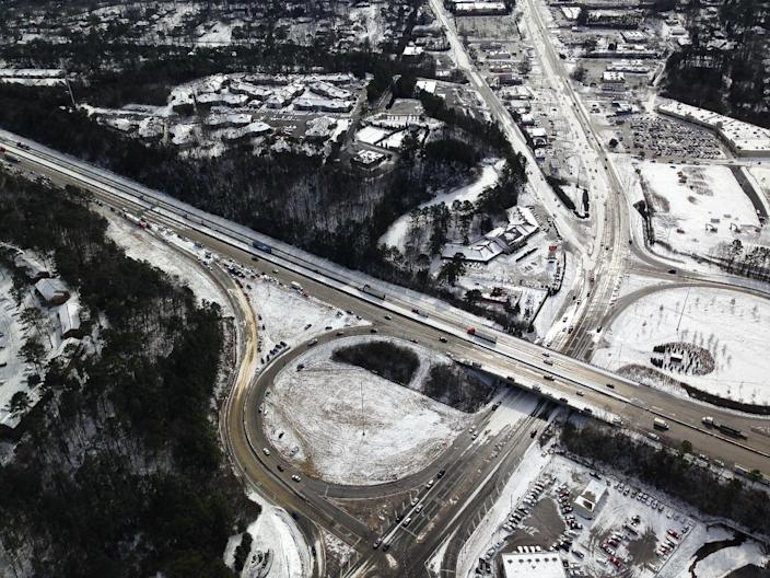 In this aerial view, vehicles sit on and near the road, Wednesday, Jan. 29, 2014, in Hoover Ala., after a winter snowstorm swept the area Tuesday. Overnight, the South saw fatal crashes and hundreds of fender-benders. Jackknifed 18-wheelers littered Interstate 65 in central Alabama. Some commuters pleaded for help via cellphones while still holed up in their cars, while others trudged miles home, abandoning their vehicles outright. (AP Photo/Jay Reeves)