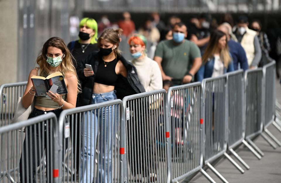 Members of the public queue to receive a dose of a Covid-19 vaccine outside a temporary vaccination centre set up at the Emirates Stadium,  (AFP via Getty Images)