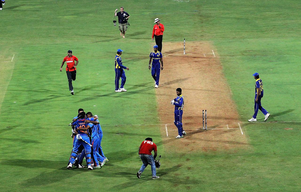 MUMBAI, INDIA - APRIL 02:  The Indian team celebrate on the field after MS Dhoni hit a six to win the match during the 2011 ICC World Cup Final between India and Sri Lanka at Wankhede Stadium on April 2, 2011 in Mumbai, India.  (Photo by Hamish Blair/Getty Images)