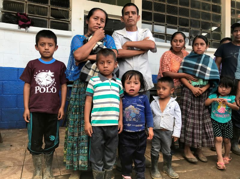 Survivor of mudslide in the village of Queja poses with her family during an interview with Reuters in the village of Chicuz