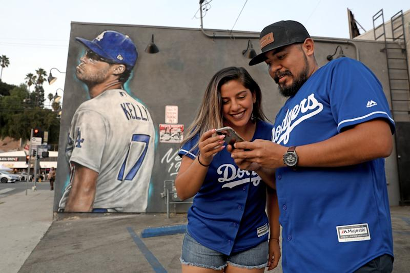 Marco Torres and Cinthya Ferrel of Los Angeles admire a photo in front of a mural of Joe Kelly making a pouty face