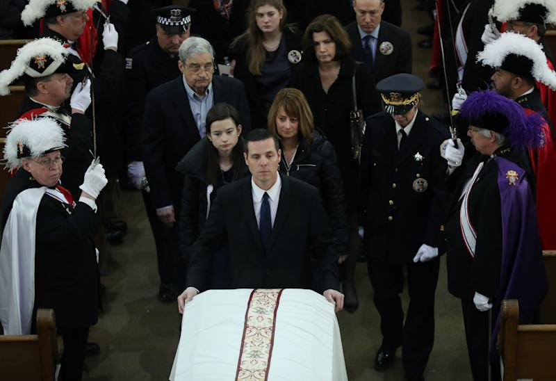 Grace Bauer, 13, and her mother, Erin Bauer, follow behind the casket of their father and husband, Chicago police Cmdr. Paul Bauer, during the recessional of his funeral mass at Nativity of Our Lord Roman Catholic Church on February 17, 2018 in Chicago, Illinois. Bauer was shot to death earlier in the week while confronting a suspect. (Photo by John J. Kim - Pool/Getty Images)